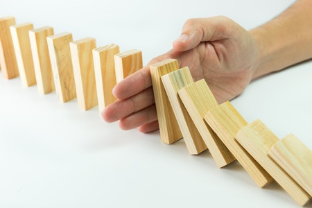 43327773 - solution concept with hand stopping wooden blocks from falling in the line of domino