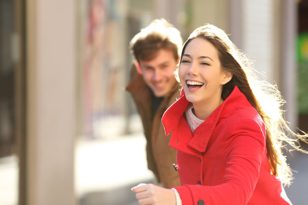 happy couple running in the street in a sunny day